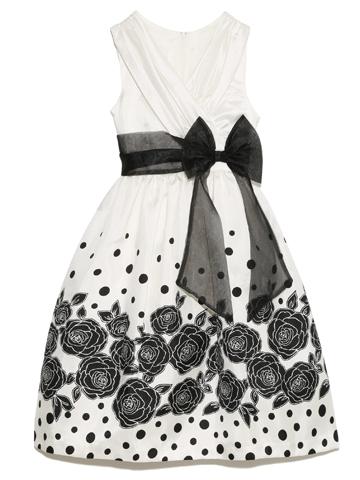 ホワイトドレスにブラックで描かれたフラワーモチーフ、胸元がカシュクール、ウエストにオーガンジーのブラックリボン。少し大人っぽく洗練されたドレス。ちょっぴり背伸びしたいお年頃のお嬢様に大人気です。