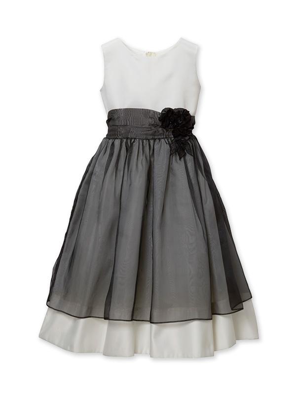 シンプルなホワイトドレスにブラックのオーガンジーが全体をエレガントにまとめあげ、ウエストのフラワーモチーフがドレスを大人可愛くみせています。