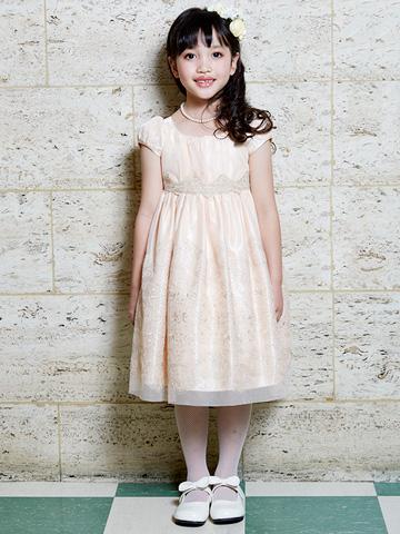 淡いオレンジのドレスにゴールドの刺繍がとても上品。後ろで結ぶサテンのリボンとパフスリーブが可愛さを一層引き立たせてくれるドレスです。