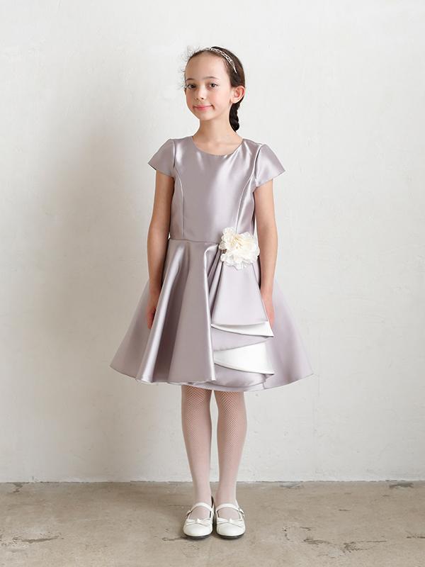 光沢がありハリのあるグレージュ生地が高級感ただようインポートドレスです。スカートのフレアー部分がシンプルなドレスに華やかさを演出しています。(モデル身長130㎝・サイズ130㎝着用写真)