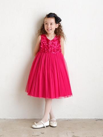 胸元あしらわれた立体的なフラワーモチーフがとても華やかで、ハイウエストがとてもキュートな印象。ビビットピンクの明るいお色目ですので舞台映えするドレスです。モデル身長120㎝・ルフィ-120㎝着用