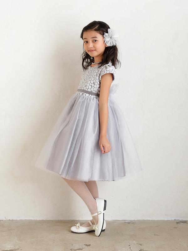 スカート部分のチュールがたっぷりあしらわれたボリュームのあるドレスです。フレンチスリーブが季節をとわないデザインで、上身頃部分にはラメ入り糸の刺繍であしらわれたドット柄が華やかな印象。ウエスト部分には、前にベルベット生地のリボン。後ろはチュール部分と同じ生地のリボンでとてもキュート。シルバーの色合いがとても上品なドレスです。(モデル身長128cm着用サイズ130cm)