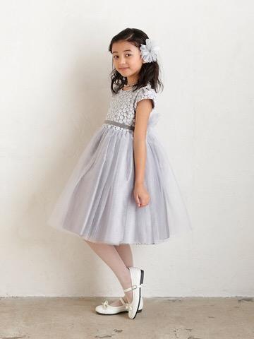 スカート部分のチュールがたっぷりあしらわれたボリュームのあるドレスです。フレンチスリーブが季節をとわないデザインで、上身頃部分にはラメ入り糸の刺繍であしらわれたドット柄が華やかな印象。ウエスト部分には、前にベルベット生地のリボン。後ろはチュール部分と同じ生地のリボンでとてもキュート。シルバーの色合いがとても上品なドレスです。