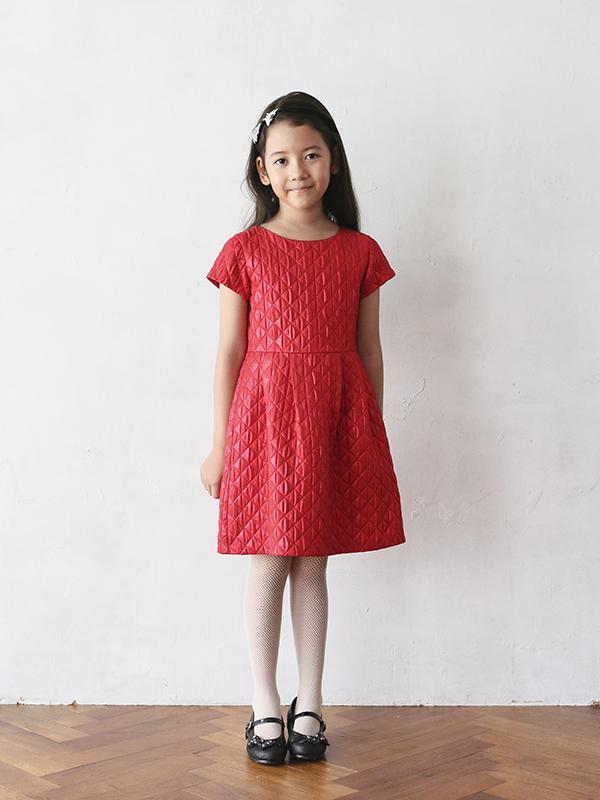 華やかで光沢のあるレッドがとても舞台映えするドレスです。シンプルなデザインですがキルティング調の生地がとてもお洒落で、長時間座っていてもシワになりにくい素材です。お袖がありますのでオールシーズン、季節問わず着ていただくことができるドレスです。120cm・140cmお取り扱いございます。