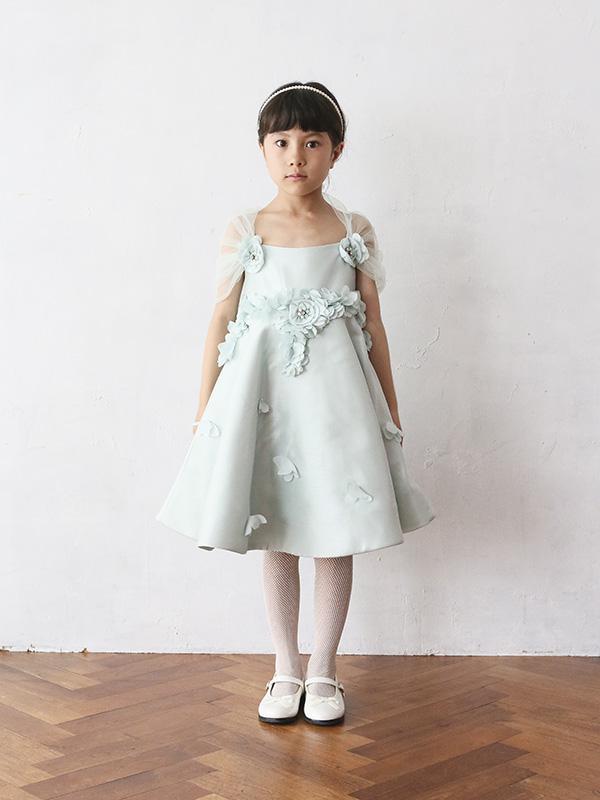 爽やかなミントグリーンのドレスには背中周りにふわっとチュールがほどこされ、ウエストラインにはお花のようなモチーフ。ところどころに蝶々がとまってるようなデザインはまるで妖精のような可愛らしいドレスです。スカート部分の裏地がしっかりしており、ハリがあるのでAラインがとてもきれいにお召し頂けます。