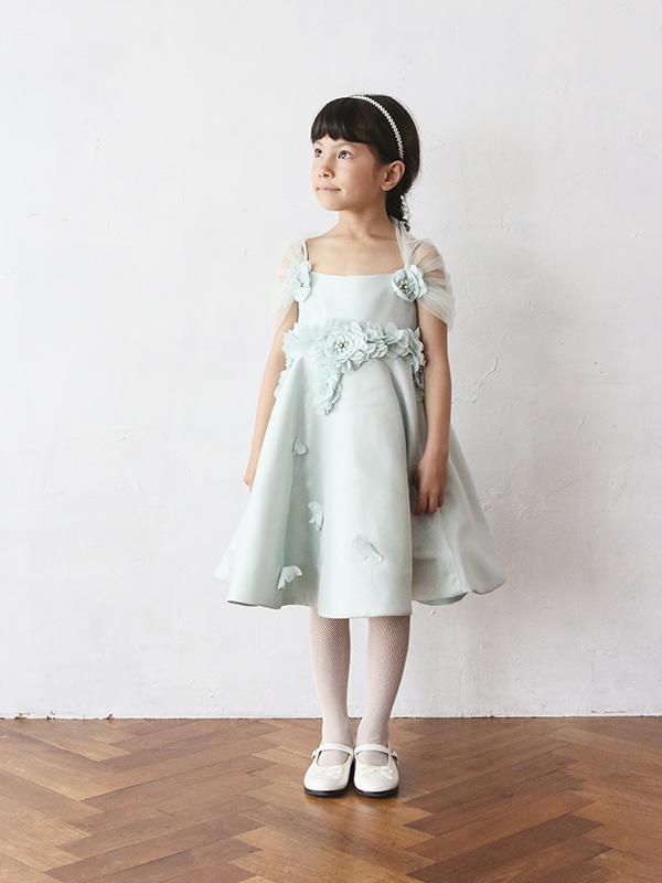 爽やかなミントグリーンのドレスには背中周りにふわっとチュールがほどこされ、ウエストラインにはお花のようなモチーフ。ところどころに蝶々がとまってるようなデザインはまるで妖精のような可愛らしいドレスです。スカート部分の裏地がしっかりしており、ハリがあるのでAラインがとてもきれいにお召し頂けます。(モデル身長110㎝着用サイズ110㎝)