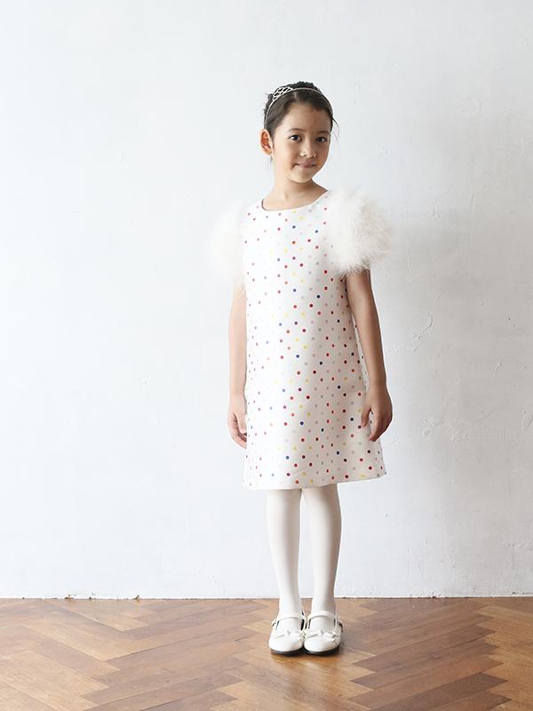 光沢のある生地にカラフルなドット柄。お袖部分のファーがモコモコしていてとっても可愛らしいドレスです。生地にはりのあるAラインタイプのドレスですのでキュートに着こなしていただける1枚です。(モデル身長120㎝着用サイズ115㎝)
