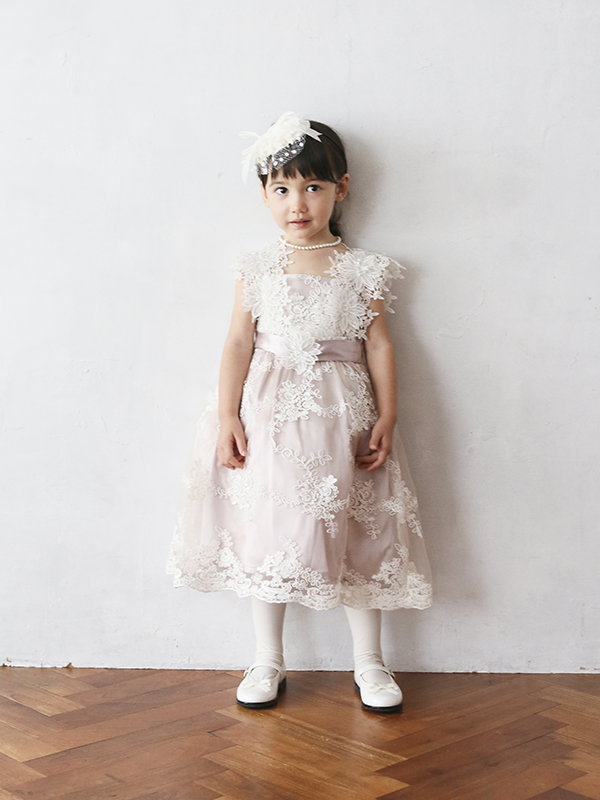 スモーキーなピンクのドレスに全体にあしらわ大きなれたフラワーレースがとても上品なドレスです。大きなフラワーの肩ひもがとても素敵な一枚です。ウエスト部分のリボンがスタイルアップ。