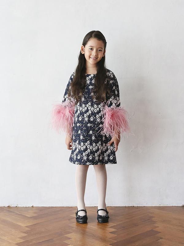 ネイビーカラーのドレスにホワイトの小花が散りばめられた柄。少し長めのお袖にピンクファーがフワフワ。Aラインがとてもキュートなコットン素材で着心地の良いドレスです。