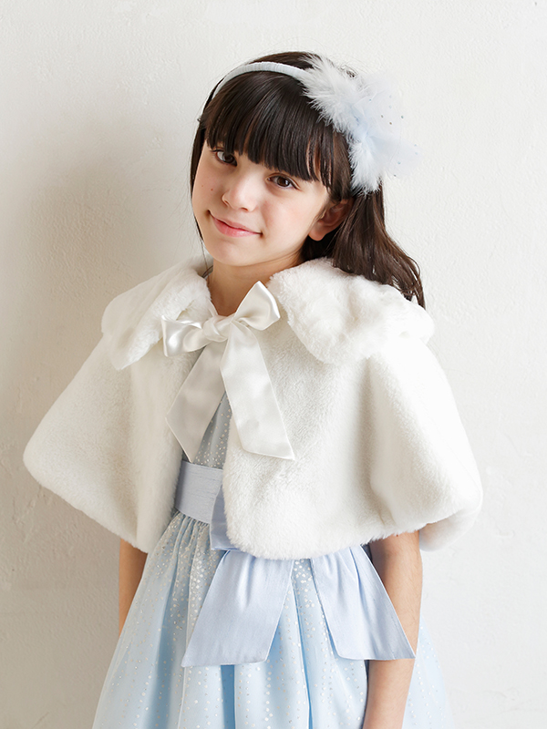 もこもこした素材がとても暖かく可愛らしいケープです。気軽に羽織れ、防寒対策にもなりどんなドレスにもお似合いの一枚です。(モデル134㎝ 着用カラーはホワイト)